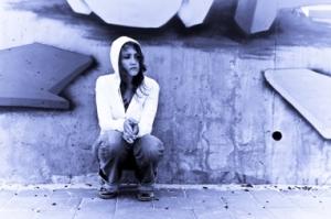 Foto av ung trist jente ved murvegg
