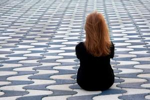 illustrasjonsfoto av jente som sitter alene på steinlagt vei
