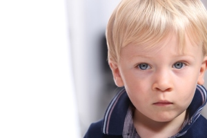 Landscape portrait of a serious little boy with blonde hair and blue eyes