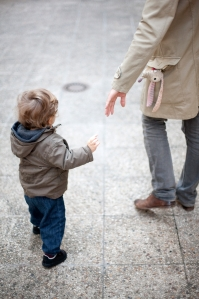 ©Sandro Di Carlo Darsa/AltoPress/Maxppp ; Father reaching for toddler's hand on sidewalk, cropped
