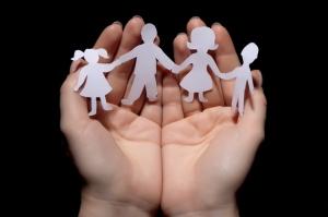 bilde av familie klipt ut i papp som holdes av hender