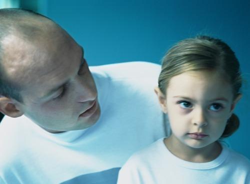 Man looking over daughter's shoulder